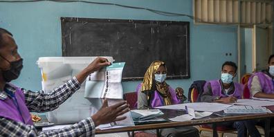 Wahlhelfer zählen Stimmen in einem Wahllokal. Die Parlamentswahl in Äthiopien wird in der Region Sidama um einen zweiten Tag verlängert. Am Wahltag habe es an Stimmzetteln gefehlt, sagte die Wahlkommission am späten Montagabend. Foto: Ben Curtis/A...