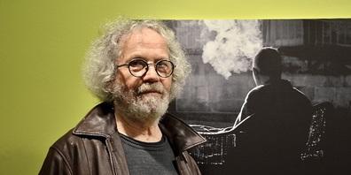 Fotograf Willi Keller vor einem seiner ästhetischen und dennoch verstörenden  Ausstellungsbilder
