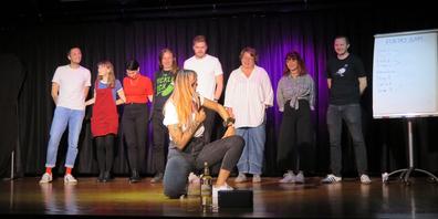 Slam-Poetinnen und Slam-Poeten aus der ganzen Schweiz standen sich in Wollerau gegenüber – vorne bewacht Moderatorin Lisa Christ den Siegerpreis, einen Quittenschnaps.