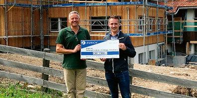 Jürg Egli, Heimleiter des Chinderhus Strahlegg, zusammen mit Pascal Lüthi, Zurich Versicherung in Klosters, bei der Übergabe des Checks auf der Baustelle.
