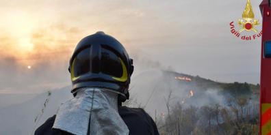 HANDOUT - Ein Feuerwehrmann steht vor einem Gebiet, in dem mehrere Brände lodern (Aufnahmeort unbekannt). Weit über 1000 Einsätze leistete die italienische Feuerwehr in den letzten 24 Stunden, um zahlreiche Waldbrände auf dem süditalienischen Fest...