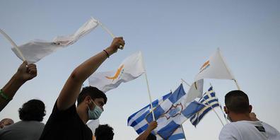 Bewohner der verlassenen Stadt Varosha oder Famagusta halten zypriotische und griechische Fahnen während eines Protestes gegen die türkische Regierung. Die Europäische Union droht der Türkei wegen der jüngsten Eskalation des Zypernkonflikts mit Sa...