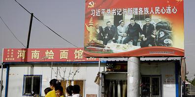 ARCHIV - Eine uigurische Frau fährt mit Schulkindern an einem Bild von Chinas Präsident Xi Jinping und einer Gruppe von uigurischen Ältesten vorbei. 43 Nationen haben am Donnerstag in einer UN-Vollversammlung Menschenrechtsverletzungen Chinas unte...