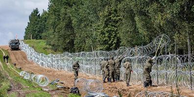 ARCHIV - Polnische Soldaten errichten einen Stacheldrahtzaun entlang der polnisch-belarussischen Grenze. Nach Einschätzung von Menschenrechtlern verschärft sich die Lage für Migranten auf dem Weg Richtung EU immer mehr. Das teilte die belarussisch...