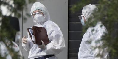 Medizinische Mitarbeiter in Schutzkleidung unterhalten sich, während sie einen Patienten mit Verdacht auf eine Coronavirus-Erkrankung in einem Krankenhaus transportieren. Die russische Hauptstadt Moskau verzeichnet weiterhin Tausende Corona-Neuinf...