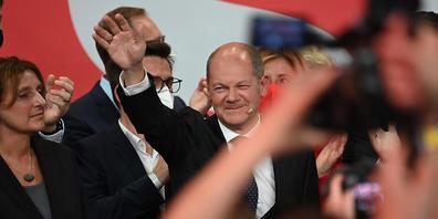 Olaf Scholz, Finanzminister und SPD-Kanzlerkandidat, winkt neben seiner Frau Britta Ernst während der Wahlparty im Willy-Brandt-Haus. Foto: Britta Pedersen/dpa