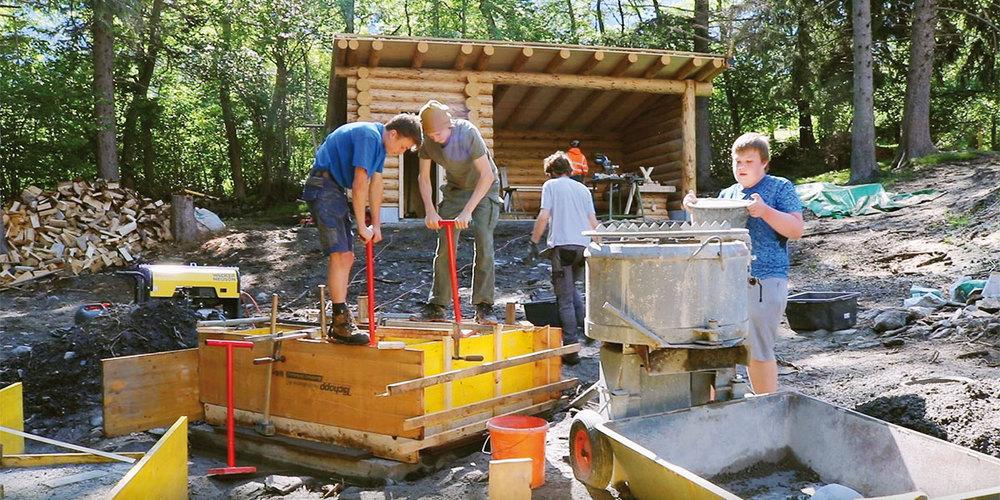 Andrin (v.l.), Florian und Enrico helfen mit vollem Körpereinsatz beim Bau der Feuerstelle.