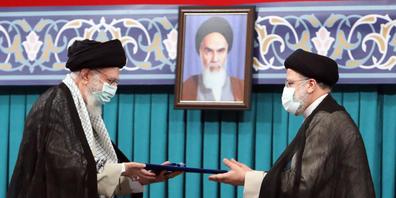 dpatopbilder - HANDOUT - Irans oberster Führer Ajatollah Ali Chamenei (l) hat die Wahl Ebrhaim Raisis zum neuen Staatspräsidenten bei einer Zeremonie bestätigt. Foto: -/Iranian Supreme Leader's Office/dpa Foto: -/Iranian Supreme Leader's Office/dp...