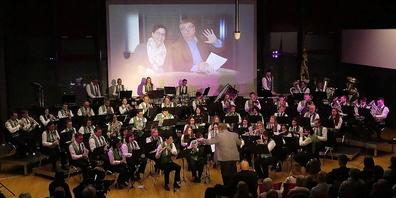 Die Musikgesellschaft Montlingen-Eichenwies bei einem der grossartigen Galakonzerte. Von der Leinwand winken Präsidentin Irene Loher und Matthias Beno