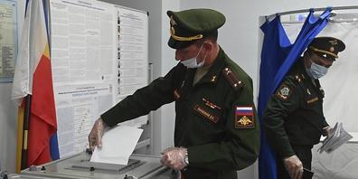 Russische Beamte geben während der Parlamentswahlen in Rostow am Don ihre Stimme in einem Wahllokal ab. Nach Beschwerden über erzwungene Stimmabgaben bei der Parlamentswahl in Russland hat die Zentrale Wahlkommission am Samstag eine Prüfung der Vo...