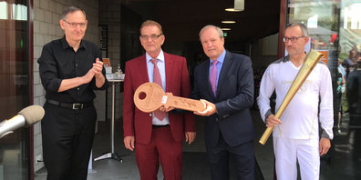 Jörg Kündig erhält von Andreas Leutenegger symbolisch den Schlüssel zur «AL Arena». Mit dabei: Regierungsrat Mario Fehr und Fackelträger Beat Kohler.