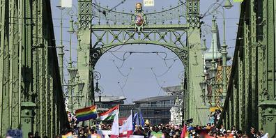 Menschen gehen bei der Gay Pride Parade über die Freiheitsbrücke in Budapest. Foto: Anna Szilagyi/AP/dpa