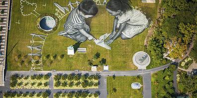 Zeichnende Kinder hat der schweizerisch-französische Künstler Saype auf den Rasen vor dem Uno-Hauptgebäude  in New York gezaubert.