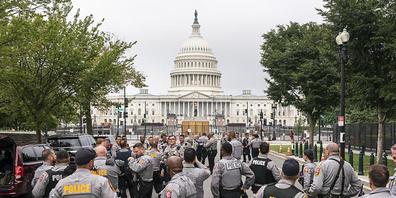Polizisten versammeln sich vor dem US-Kapitol in Washington. Gut acht Monate nach der Erstürmung des Kapitols hat sich die US-Hauptstadt für eine Demonstration von Anhängern des damaligen US-Präsidenten Donald Trump vorbereitet. Foto: Nathan Howar...