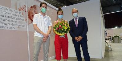 Überreichten einen Blumenstrauss an die Frau, welche  mit ihrer zweiten Impfung die 50'000er-Marke geknackt hat: Lukas Resemann, Leiter Impfen (links) und Jörg Kündig, Gemeindepräsident von Gossau ZH.