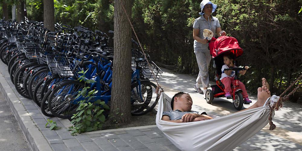 ARCHIV - Ein Mann schläft in einer Hängematte neben Fahrrädern einer Fahrrad-Verleihfirma. Viele junge Chinesen haben das Gefühl, alles hinschmeißen zu wollen. Foto: Ng Han Guan/AP/dpa