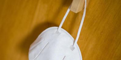 ARCHIV - Eine FFP2-Maske hängt an einem Haken. Island will seine Corona-Maßnahmen lockern. Dazu gehört unter anderem, dass der Mund-Nasen-Schutz bei Veranstaltungen nicht länger getragen werden muss. Foto: Daniel Karmann/dpa