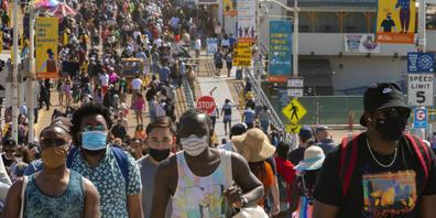 ARCHIV - Menschen drängen sich am Santa Monica Pier. In den USA nimmt die Zahl der an einem Tag erfassten Corona-Neuinfektionen wieder zu. Foto: Damian Dovarganes/AP/dpa