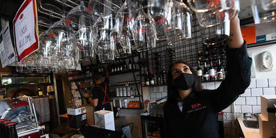 Staff member Nicoletta Alberici restocks glassware at 48h Pizza and Gnocchi Bar ahead of their reopening tomorrow in Elsternwick, Melbourne, Thursday, October 21, 2021. A further 2232 local COVID-19 cases and 12 deaths have been reported in Victor...