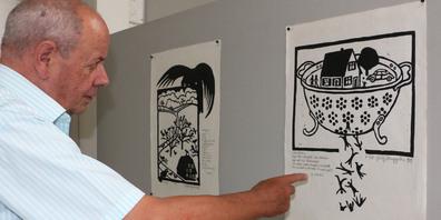 Ueli Eberhardt zeigt den Holzschnitt «Löcherbecki» von 1989, der auf die Vergänglichkeit des Menschen aufmerksam macht.