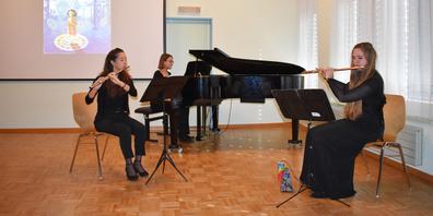 Die drei Musikerinnen während des Auftritts, auf der Leinwand im Hintergrund die Bilder zur Geschichte.