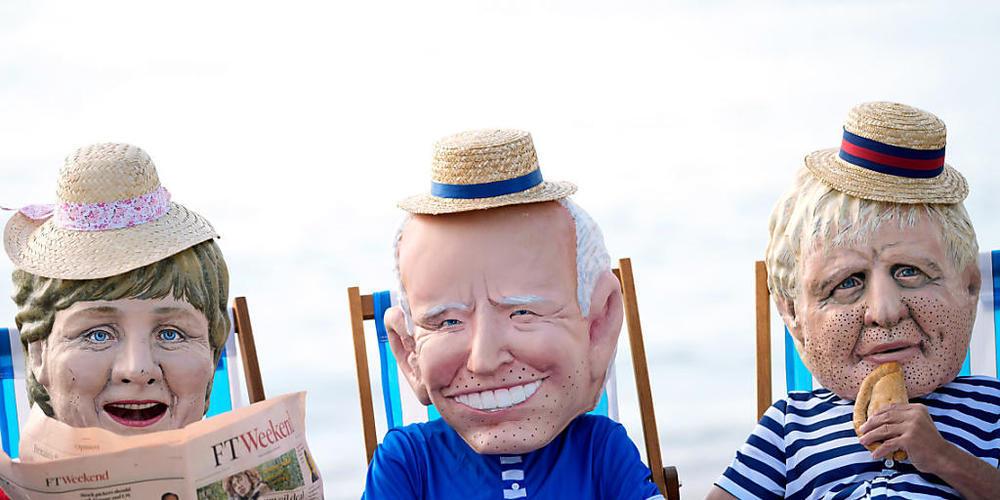 Klimaaktivisten von Oxfam, die riesige Köpfe tragen, die die Staats- und Regierungschefs der G7 (l-r) Bundeskanzlerin Angela Merkel, US-Präsident Joe Biden, der britische Premierminister Boris Johnson darstellen sollen, sitzen auf Strandliegen, wä...