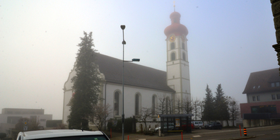 Die Pfarrkirche St. Jakobus in Gommiswald an einem nebligen Herbsttag.