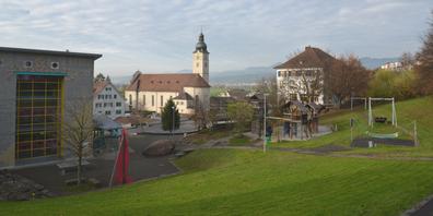 Benken befindet sich teilweise am Fuss eines Hügels. Blick auf den Spielplatz beim Schulhaus Oberdorf und die katholische Kirche.