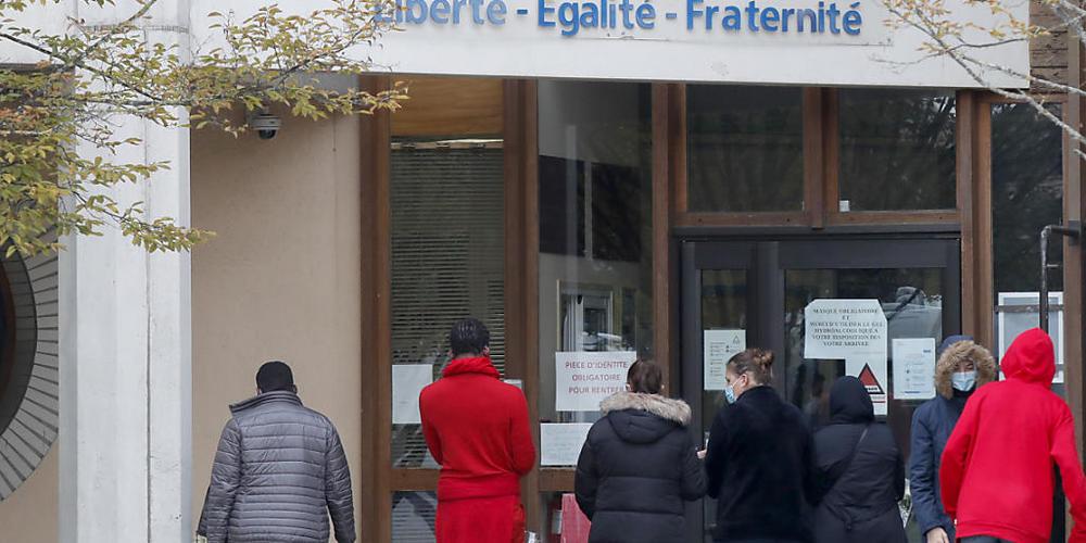 Schüler gedenken vor einer Schule, auf der der Schriftzug «Liberté - Egalité - Fraternité» (Freiheit - Gleichheit - Brüderlichkeit) zu lesen ist, einem Lehrer, der bei einer mutmaßlich terroristisch motivierten Tat ermordet wurde. Foto: Michel Eul...