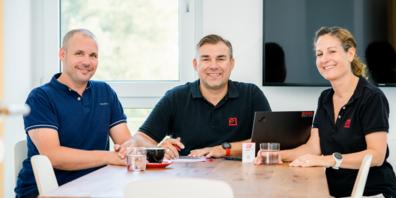 Die Inhaber beider Firmen bei der Vertragsunterzeichnung. Von links nach rechts: Fabian Elser von der KF data AG; Martin Harzl und Gioia Harzl-Fatzer von der HARZL ICT GMBH.