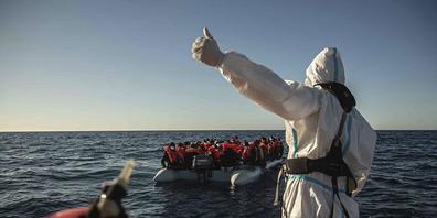 ARCHIV - Ein Mitarbeiter der spanischen NGO «Open Arms» steht auf einem Boot vor der libyschen Küste. Etwa vier Jahre nach der Festsetzung der «Iuventa» in Italien fordert Amnesty International eine Entkriminalisierung der Seenotrettung. Diese sei...