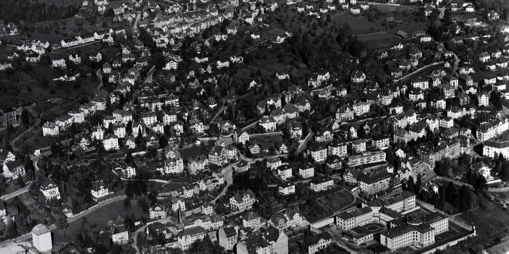 Ein Panoramablick auf das Quartier St. Jakob des Jahres 1945: Wir sehen den Schellenacker und die Viertel St.Jakob, Leimat sowie Rotmonten. Prägnant unten rechts im Bild die Strafanstalt St. Jakob (gebaut 1836-39, abgebrochen 1958). In der Bildmitte das alte Gebäude der Brauerei Schützengarten mit Kamin an der St. Jakob-Strasse 35 (gebaut 1884/85, abgebrochen 2000).