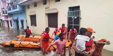 HANDOUT - Dieses von der indischen National Disaster Response Force (NDRF) zur Verfügung gestellte Foto zeigt NDRF-Soldaten bei der Rettung von Menschen, die im indischen Udham Singh Nagar in den Fluten festsitzen. Bisher sind mindestens 34 Mensch...