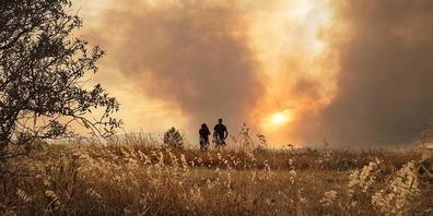 Menschen beobachten einen Waldbrand in Südfrankreich. Im Kampf gegen den Brand zwischen den Städten Narbonne und Carcassonne sind über 1000 Feuerwehrleute und Retter im Einsatz. Foto: Idriss Bigou-Gilles/AFP/dpa