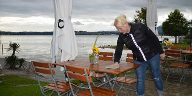 Alles andere als sommerlich: Ana Pipenbaher putzt die nassen Tische im Seebad Altendorf. Sie hat noch bis Donnerstag geöffnet.