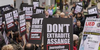 Unterstützer des inhaftierten Wikileaks-Gründers Assange halten während einer Demonstration Plakate in die Höhe. Die Menschenrechtsorganisation Amnesty International hat am Dienstag vor einer Anhörung im Fall Julian Assange erneut die Freilassung ...