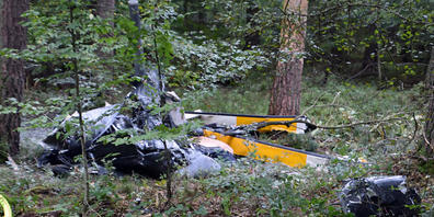 Trümmerteile eines Hubschraubers liegen in einem Wald nahe der Grenze zu Hessen und Bayern. Foto: Julian Buchner/Einsatz-Report24/dpa