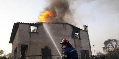 Ein Feuerwehrmann löscht einen Brand an einem Gebäude, der durch das Feuer von Waldbrände entfacht ist. Feuerwehrleute in Griechenland kämpfen auch am Mittwochmorgen weiter gegen den Großbrand in den nördlichen Vorstädten Athens. Regierungschef Ky...