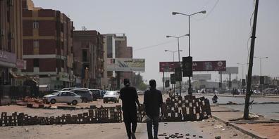 Zwei Personen gehen auf einer Straße auf der Steine liegen und eine behelfsmäßigen Barrikade aufgebaut ist. Nach dem Militärputsch am 25. Oktober 2021, bei dem das Militär die Macht über das Land übernommen hat, ist der entmachtete Ministerpräside...