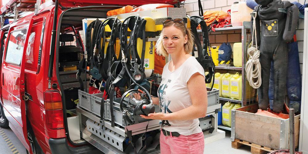 Désirée Mäder zeigt bei der Führung durchs Feuerwehr-Depot die Maske eines Atemschutzgeräts.
