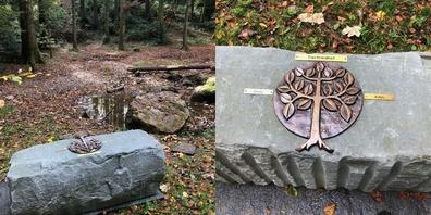 Auf der stillen Lichtung steht ein Grabstein mit den Namenschildern der bestatteten Tiere.