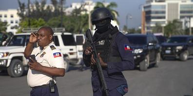Bewaffnete Sicherheitskräfte stehen auf einer Straße in Port-Au-Prince. Foto: Joseph Odelyn/AP/dpa
