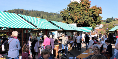 Hochbetrieb auf dem Marktplatz, mit Aussicht auf die herbstliche Natur.