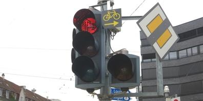 Das Schild mit gelbem Velo auf schwarzem Grund neben der Ampel erlaubt Velos das Rechtsabbiegen bei Rot.