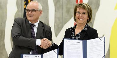 Der Berner Regierungsrat Pierre Alain Schnegg und seine jurassische Amtskollegin Nathalie Barthoulot mit der unterzeichneten Roadmap für Moutier.