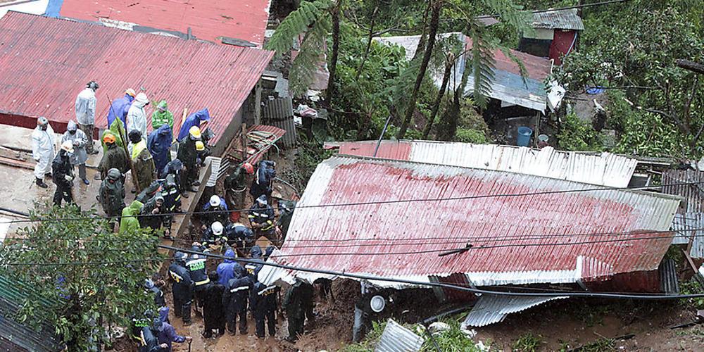 Rettungskräfte auf den Philippinen suchen in einem Haus nach Opfern. Das Haus wurde durch den Tropensturm Kompasu verursachten Erdrutsch verschüttet. Foto: Uncredited/AP/dpa